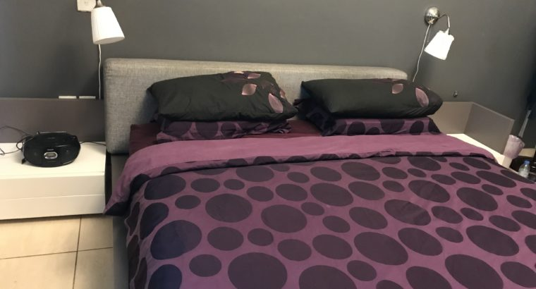 King size bed with two night tables and a mattress